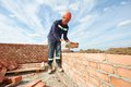 Construction mason worker bricklayer installing red brick with trowel putty knife outdoors Royalty Free Stock Images