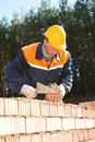 Construction mason worker bricklayer installing red brick with trowel putty knife outdoors Royalty Free Stock Photos