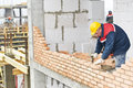 Construction mason worker bricklayer installing red brick with trowel putty knife outdoors Stock Photo