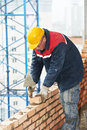 Construction mason worker bricklayer installing red brick with trowel putty knife outdoors Royalty Free Stock Image