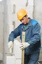 Construction mason worker bricklayer with level inspecting installation of calcium silicate brick during indoor wall creation Stock Image