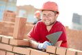 Construction mason worker bricklayer portrait of installing red brick with trowel putty knife outdoors Royalty Free Stock Photos