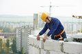 Construction mason worker bricklayer working with limestone brick and measuring tape outdoors Royalty Free Stock Photo