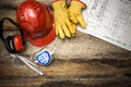Construction protective workwear with plans background on rustic floor boards Royalty Free Stock Image