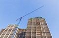 Construction of a residential skyscraper low angle view the with an industrial crane working on the external facade the Royalty Free Stock Image