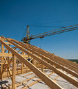 Construction of a roof worker working on the installation timber frame house and crane Royalty Free Stock Photos