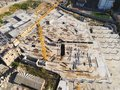 Construction site aerial view. Mall building base with solid concrete pillars. Heavy machinery and high tower crane Royalty Free Stock Photo