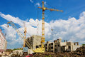 Construction site cranes on the beneath blue cloudy sky Royalty Free Stock Images