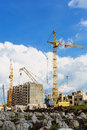 Construction site cranes on the beneath blue cloudy sky Royalty Free Stock Image