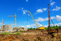 Construction site cranes on the beneath blue cloudy sky Royalty Free Stock Photo