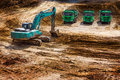 Construction site excavator and trucks parked in waiting for work Royalty Free Stock Photo