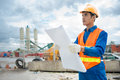 On construction site image of a foreman with a blueprint the Royalty Free Stock Images