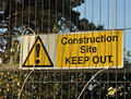 Construction site keep out sign on metal fence with trees behind it Royalty Free Stock Images