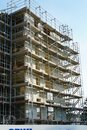 Construction site of a large residential building, its facade covered  with scaffolding Royalty Free Stock Photo
