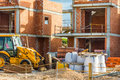 Construction site red brick residential townhouses, concrete pillars, digger, piles of materials, unfinished new build Royalty Free Stock Photo