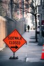 Red orange caution city sign with side walk closed black text Royalty Free Stock Photo
