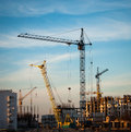 Construction site at sunset with building cranes industrial landscape with cranes on the cloudy sky Stock Image