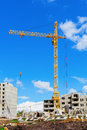 Construction site tower crane on the beneath blue cloudy sky Stock Photography