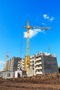 Construction site tower crane on the beneath blue cloudy sky Royalty Free Stock Photos