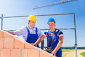 Construction site workers building house with crane two proud or bricklayers standing on project directing the a remote control Royalty Free Stock Images