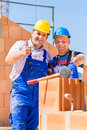 Construction site workers building walls on house worker a home or doing bricklaying work the of the shell Royalty Free Stock Images