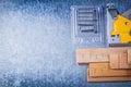 Construction stapler chrome staples wood building board on metal metallic background Stock Photo