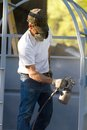 Construction steel worker uses paint sprayer to apply primer coat to metalwork Royalty Free Stock Photography