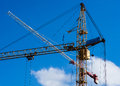 Construction symphony two tower cranes against the background of blue sky and white cloud Stock Images