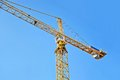 Construction tower crane yellow against blue sky Stock Photos