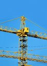 Construction tower crane yellow against blue sky Stock Image