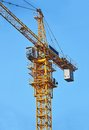 Construction tower crane yellow against blue sky Stock Photo