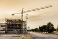 Construction an unfinished building at dusk with a yellow crane near it Royalty Free Stock Images