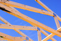 Construction wood frame of a roof against a blue sky Stock Photos