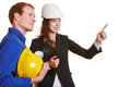 Construction worker and architect in a jump suit working together Stock Photos