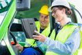 Construction worker discussing with engineer blueprints in machinery on pad or tablet computer on site Stock Photos