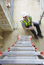 Construction Worker Falling Off Ladder And Injuring Leg Royalty Free Stock Photo