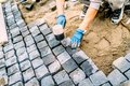 construction worker, handyman using cobblestone granite stones for creating walking path. Terrace or sidewalk details