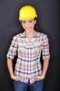 Construction worker happy woman portrait young wearing safety glasses and yellow hard hat for security and protection multiracial Stock Image