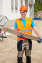 Construction worker holding wooden beam in protective workwear Stock Image