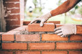 construction worker laying bricks and building barbecue in industrial site. Detail of hand adjusting bricks Royalty Free Stock Photo