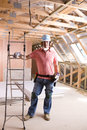 Construction worker leaning on ladder in attic Royalty Free Stock Photo