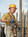 Construction worker making reinforcement builder knitting metal rods bars into framework for concrete pouring at site Stock Image