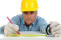 Construction worker measuring and marking closeup of a in hard hat using a tape to mark cut line on a board focus is on the mans Royalty Free Stock Images