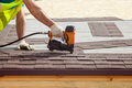 Construction worker putting the asphalt roofing shingles with nail gun on a new frame house. Royalty Free Stock Photo