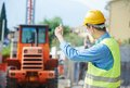 Construction worker in safety protective work wear ruling machinery loader at building area Royalty Free Stock Photo