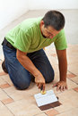 Construction worker testing the joint color on ceramic tiles flo floor spreading it with a spatula Stock Photography
