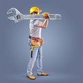 Construction worker with a tool belt and a wrench on blue background Stock Image