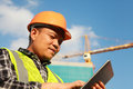Construction worker using digital tablet with crane on the background Royalty Free Stock Photos