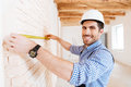 Construction worker using measuring tape in a new house Royalty Free Stock Photo