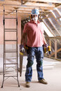 Construction worker wearing protective mask and holding tools in attic Royalty Free Stock Photo